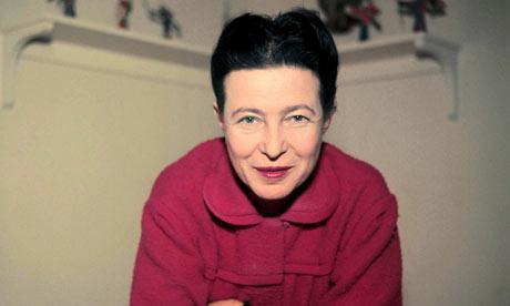 Farbfoto, das Simone de Beauvoir in einem roten Mantel freundlich lächelnd zeigt.